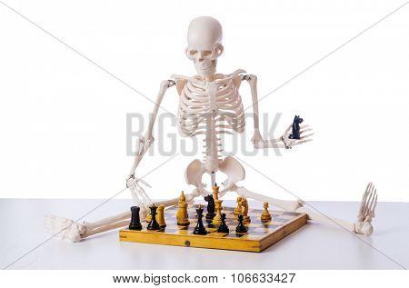 Skeleton playing chess game on white