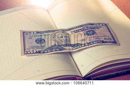 Fifty American Dollars And Notepad On Wooden Table