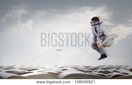 Young businessman in suit and diving mask jumping in pile of books
