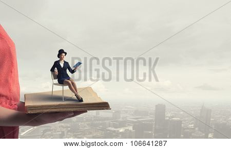 Pretty girl wearing retro hat siting on chair with book in hands