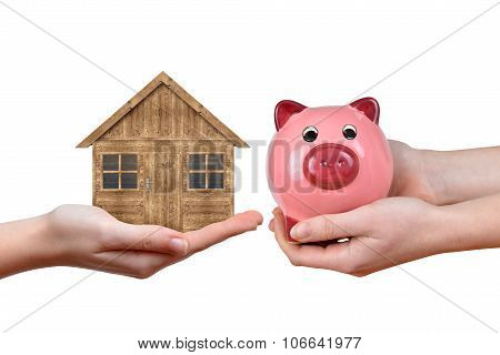 Hands holding wooden house and pink piggy bank