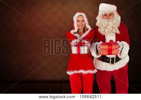 Santa and Mrs Claus smiling at camera offering gift against room with wallpaper