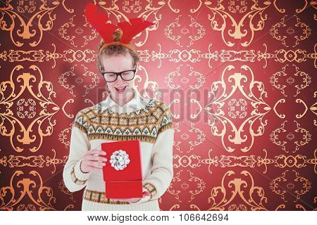 Surprised geeky hipster opening present against elegant patterned wallpaper in red and gold