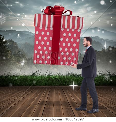 Stylish man with giant gift against mountain range beyond wooden floor