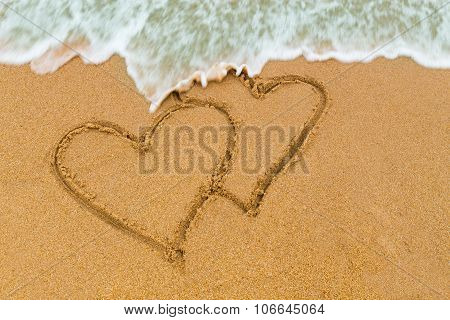 Twin Double Heart Drawn On Sandy Beach With Wave Approaching