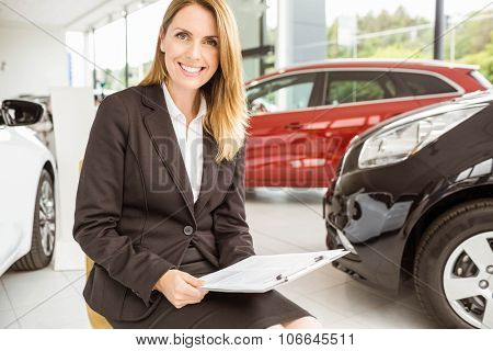 Smiling saleswoman sitting near cars at new car showroom