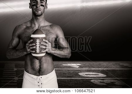 Portrait of shirtless player holding rugby ball against spotlight