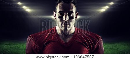 American football player looking at camera against rugby stadium