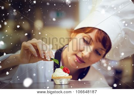 Snow against focused head chef putting mint leaf on little cake