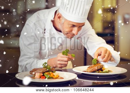 Snow against concentrated male chef garnishing food in kitchen