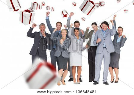 Excited business team cheering at camera against white and red gift box