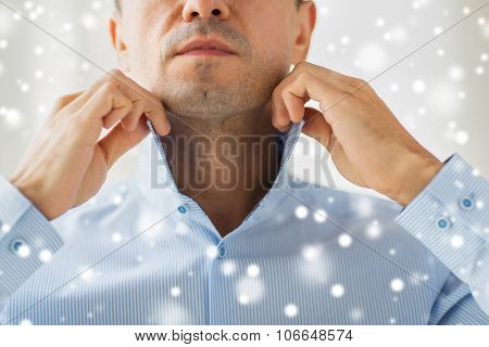 people, business, fashion and clothing concept - close up of man dressing up and adjusting shirt collar at home over snow effect