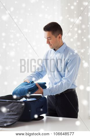 business, trip, luggage and people concept - happy businessman packing clothes into travel bag over snow effect over snow effect