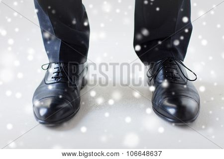 people, business, fashion and footwear concept - close up of man legs in elegant shoes with laces or lace boots over snow effect over snow effect