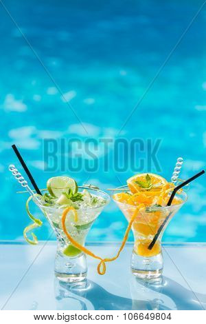 Mohito mojito drink with ice mint, orange and lime near swimming pool