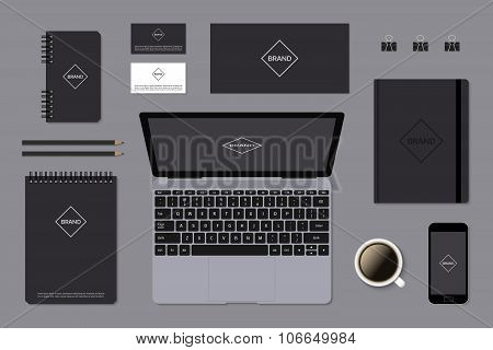 Dark identity mock-up template on gray background with laptop.