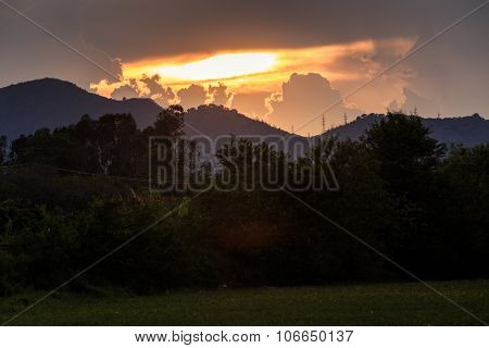 View Of Rising Sunbeams From Behind Clouds In Mountains