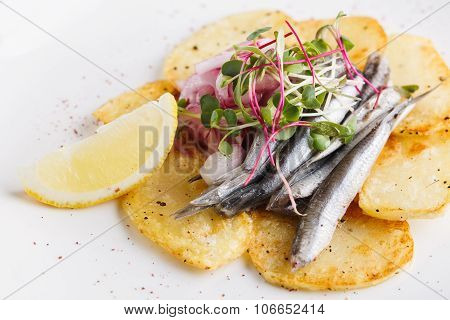 Anchovies With Potatoes And Vegetables On A Plate