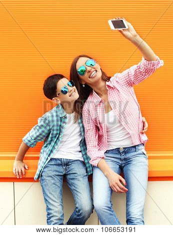 Happy Mother And Son Teenager Taking Picture Self Portrait On Smartphone In City, Over Colorful Back