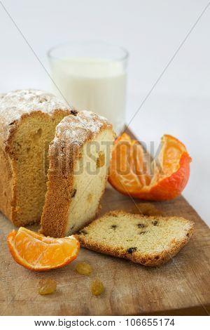 cake cupcake raisins milk tangerine on wooden surface