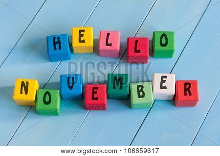 Word Hello November On child's toy cubes on wooden rural  background.