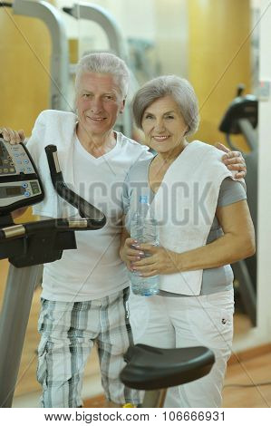 Senior couple drinking in gym