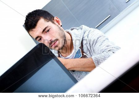 Young Man With Laptop In The Kitchen