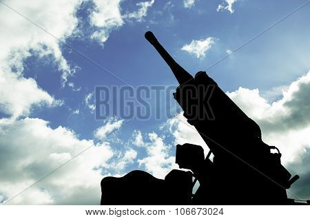 Silhouette Of An Anti-aircraft Cannon On A Background Of Clear Sky