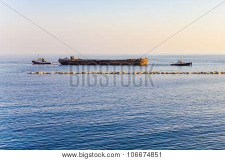 Two Tugboats Hauling A Barge .
