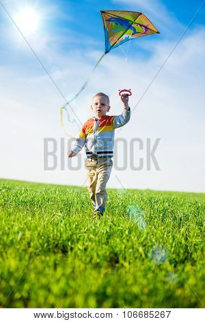 Young boy playing with his kite in a green field.
