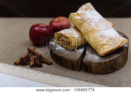 Apple Strudel On Wooden End Of A Tree With Apples, Cinnamon And Star Anise