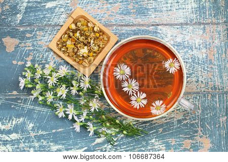 Cup of chamomile tea with fresh chamomile flowers on rustic wooden surface