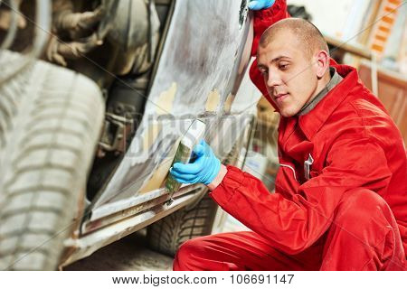 auto mechanic worker sanding body car at automobile repair and renew service station shop by sandpaper