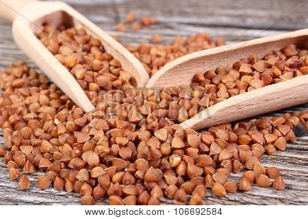 Heap Of Buckwheat Groats With Spoon On Wooden Surface