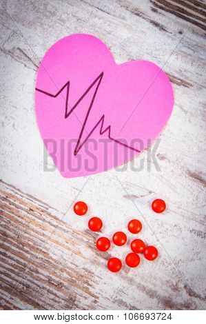 Heart Of Paper With Cardiogram Line And Supplement Pills, Medicine And Healthcare Concept