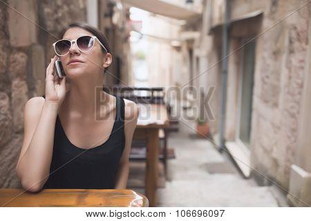Beautiful dark tan European woman talking on the phone with friend gossiping. Business woman talking