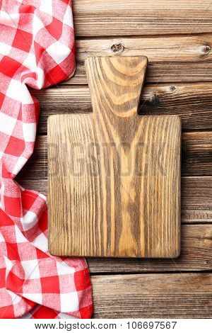 Empty Wooden Table With Cutting Board And Napkin On Brown Background