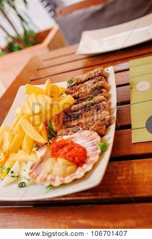 traditional slovenian and croatian cuisine, grilled meat kebab - chevapchichi with french fries