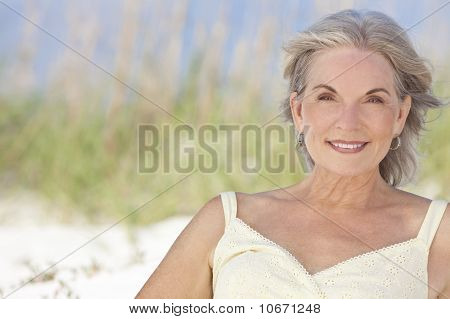 Attractive Elegant Senior Woman Sitting At A Beach