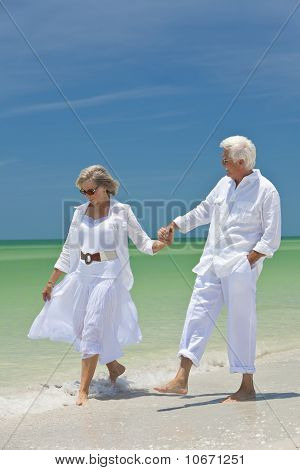 Happy Senior Couple Walking Holding Hands On A Tropical Beach