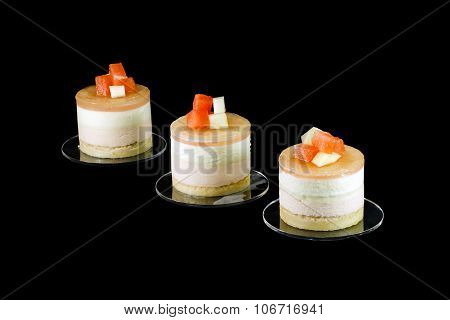 Three small cakes decorated with different fruits