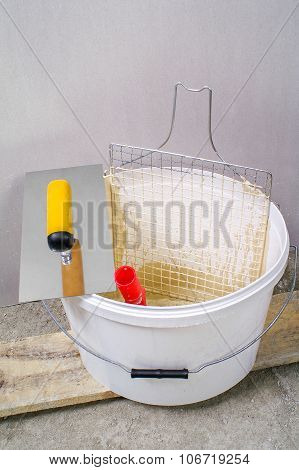 Painter Bucket With Net, Trowel And Roller In Front Of Gypsum Wall