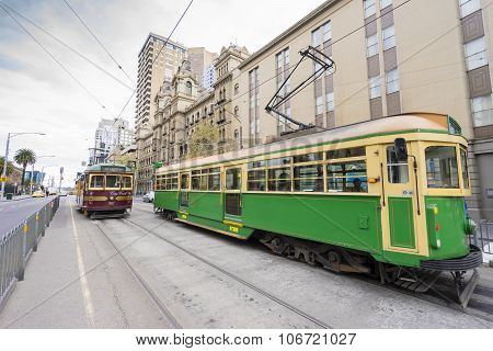 People and vintage trams on the street in Melbourne