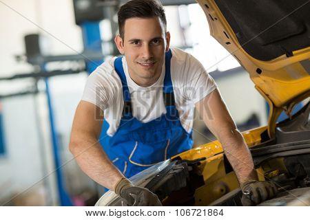 Smiling mechanic working on engine on car