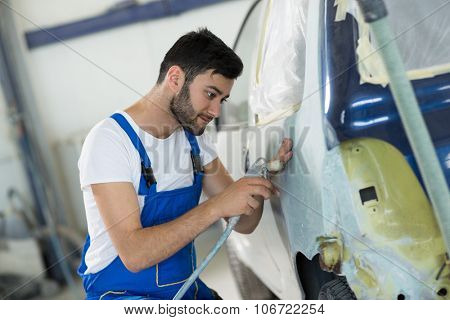 Worker prepare body part for paint in service