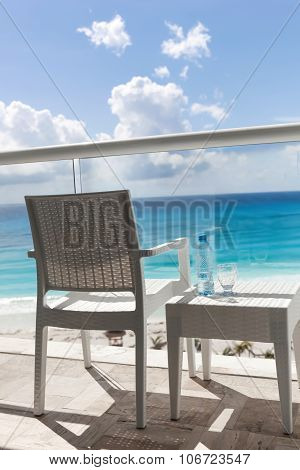 Balcony With Plastic Bottle Of Water On  Table Overlooking An Ocean
