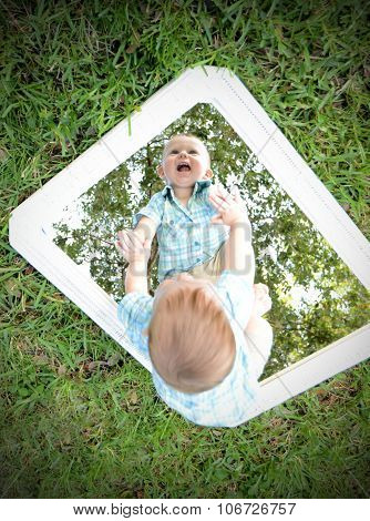 Young Baby Looking At Self In Mirror While Smiling