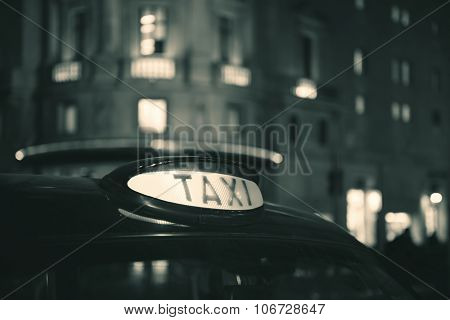Vintage taxi in street in London at night.
