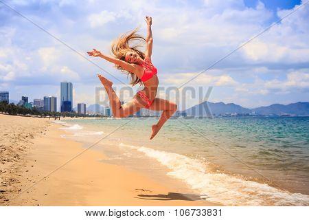 Blonde Slim Gymnast In Bikini In Jump Over Beach Against Sky