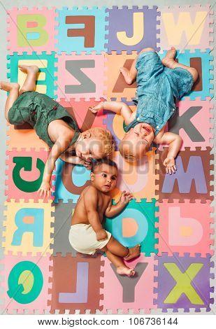 Multiethnic babies lying around on  Alphabet puzzle background
